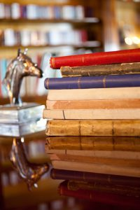 Antique books over a wooden luxury table. Defocused bookshelf on the back and a small metal horse head. Reflection on table.